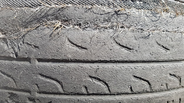 Um pneu que se danifica após um uso prolongado. um pneu de carro gasto e rasgado em um ferro-velho.