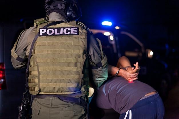 Um policial algema as mãos de um criminoso durante uma prisão. carro de polícia com faróis piscando. copie o espaço