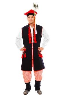 Um polonês em traje tradicional de pé sobre um fundo branco