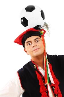 Um polonês em uma roupa tradicional com uma bola de futebol na cabeça