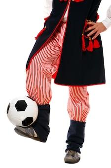 Um polonês em uma roupa tradicional com uma bola de futebol