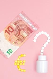 Um ponto de interrogação e uma marca de euro dispostos em comprimidos e 10 euros em uma parede rosa. conceito de medicina, dinheiro e saúde