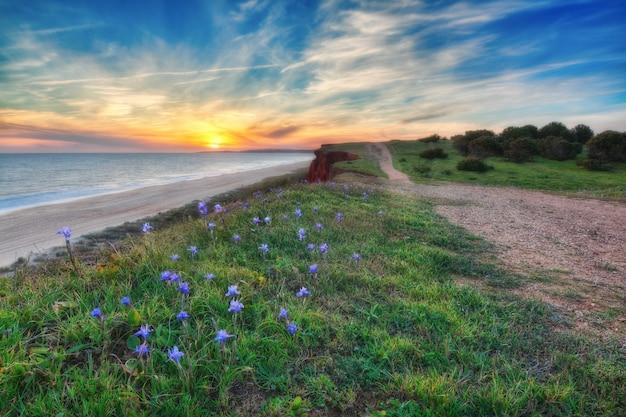 Um por do sol bonito com cores do mar e dos azul-céu. perto da estrada.