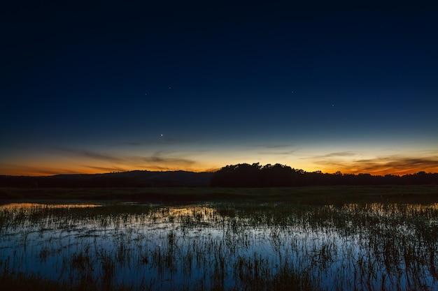 Um pôr do sol brilhante no céu noturno. a paisagem com o rio e as árvores é fotografada em longa exposição.