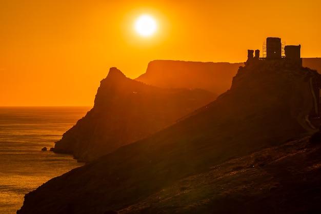 Um pôr do sol em chamas vermelhas com a silhueta de um penhasco e um castelo sobre o mar