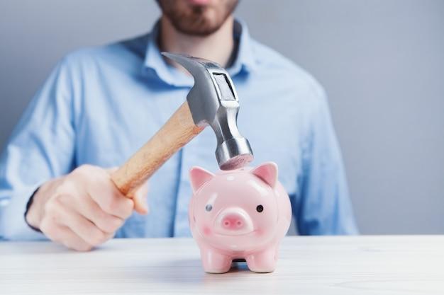 Um porquinho rosa triste está prestes a ser atingido por um martelo em um tom vintage. problema financeiro
