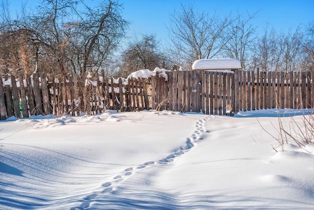 Um portão em uma cerca de madeira e pegadas na neve