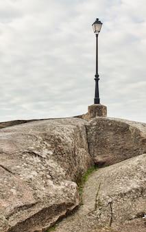 Um poste de ferro solitário em uma rocha de granito em uma cidade da extremadura, um poste de luz incomum