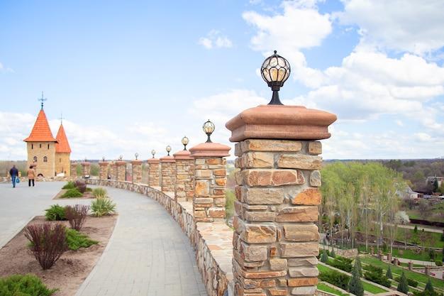 Um poste de luz no parapeito do parque, decorado com elementos de ferro forjado. iluminação pública. cerca de pedra