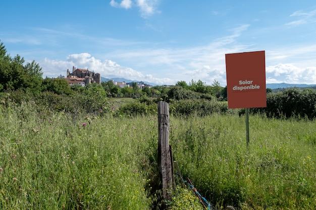Um pôster anuncia a venda de um terreno rural perto de uma cidade medieval em que sua catedral