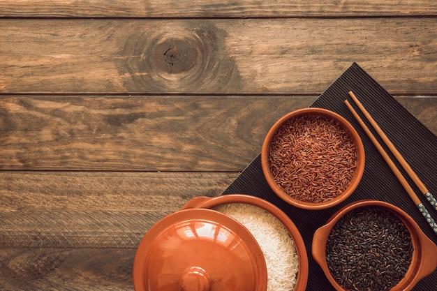Um pote aberto e tigelas com diferentes tipos de grãos de arroz na mesa de madeira