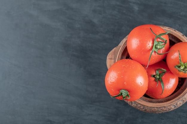 Um pote antigo com tomates frescos em um fundo escuro.