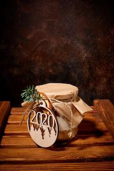 Um pote cheio de especiarias doces é coberto com papel kraft e amarrado com barbante; um medalhão com os números do ano novo é amarrado a ele, que fica sobre um palete de madeira