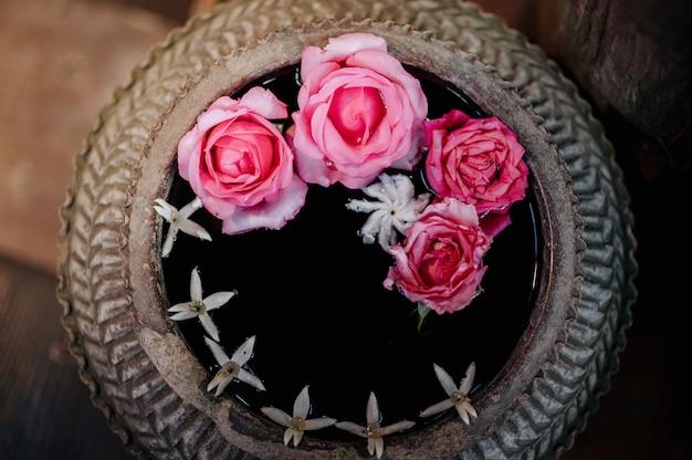 Um pote de água com rosas e outras flores flutuando lá