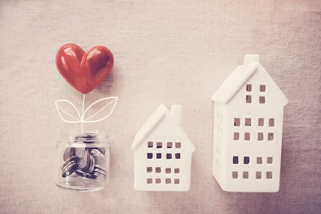 Um pote de árvore coração crescendo em moedas de dinheiro e casas modelo