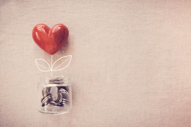 Um pote de árvore do coração que cresce em moedas de dinheiro, responsabilidade social e conceito de doação