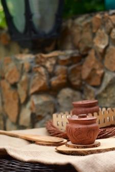 Um pote de barro com mel em uma bandeja natural de madeira serrada contra uma parede de pedra. banner vertical