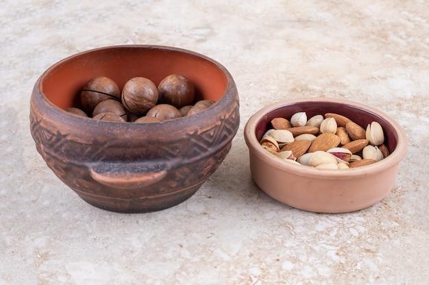 Um pote de bolas de chocolate e uma pequena tigela de nozes sortidas