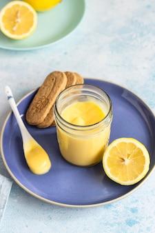 Um pote de coalhada de limão ou creme e biscoitos num prato azul.