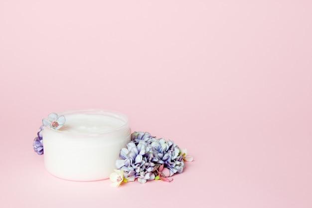 Um pote de creme com flores em rosa