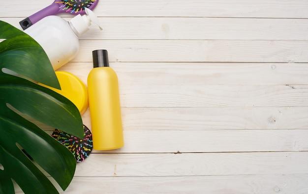 Um pote de creme hidratante e um pente em uma folha de palmeira de mesa de madeira. foto de alta qualidade