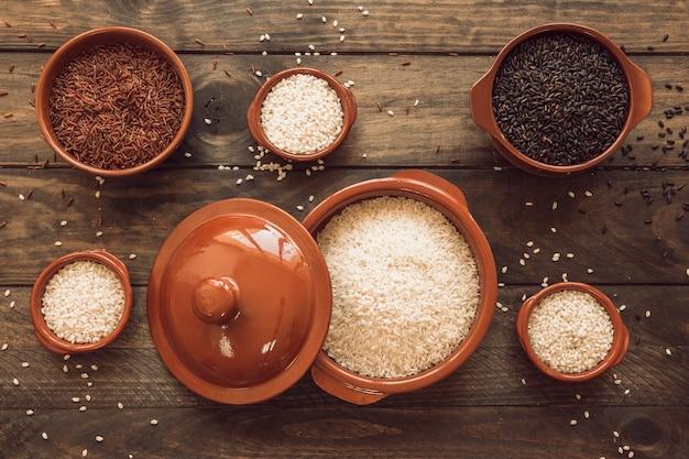 Um pote de grãos de arroz orgânico com tigelas na mesa de madeira