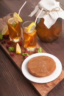 Um pote de kombuchá, dois copos de uma bebida, canudos e rodelas de limão, framboesas estão em uma mesa de madeira.