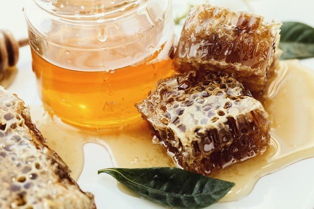 Um pote de mel com folhas verdes ao redor