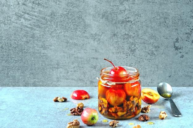 Um pote de mel com pequenas maçãs e nozes.