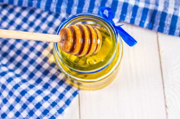 Um pote de mel com uma colher, sobre uma mesa branca com uma toalha azul