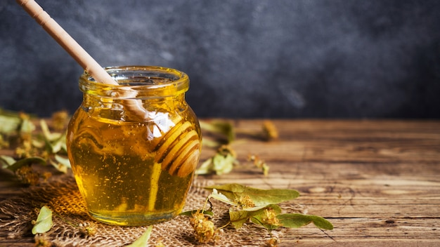 Um pote de mel líquido de flores de tília e um palito com mel em um fundo escuro. copie o espaço
