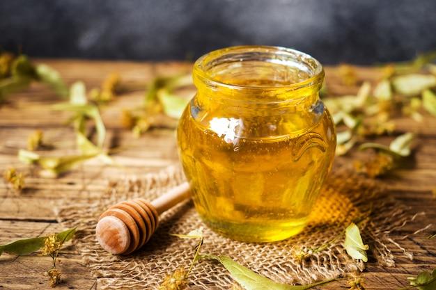 Um pote de mel líquido de flores de tília e um pau com mel em uma superfície escura.
