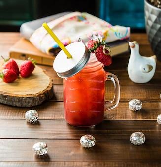 Um pote de smoothie de morango com cubos de gelo.