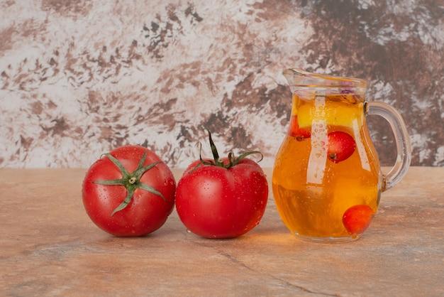 Um pote de suco e tomates frescos na mesa de mármore.