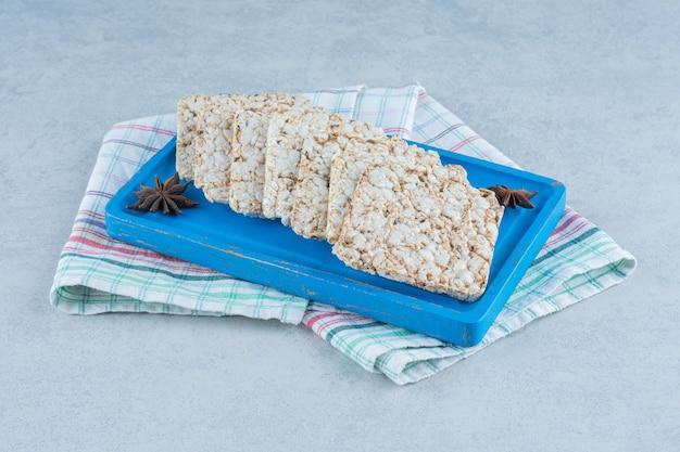 Um pouco de bolo de arroz e canela a bordo em mármore.