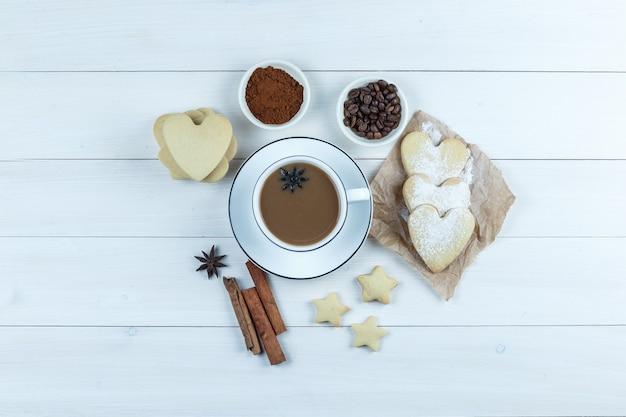 Um pouco de café com biscoitos, especiarias, grãos de café, café moído em uma xícara com fundo de madeira, vista superior.