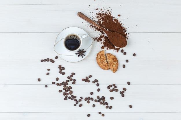 Um pouco de café com café moído, especiarias, grãos de café, biscoitos em uma xícara com fundo de madeira, plana leigos.