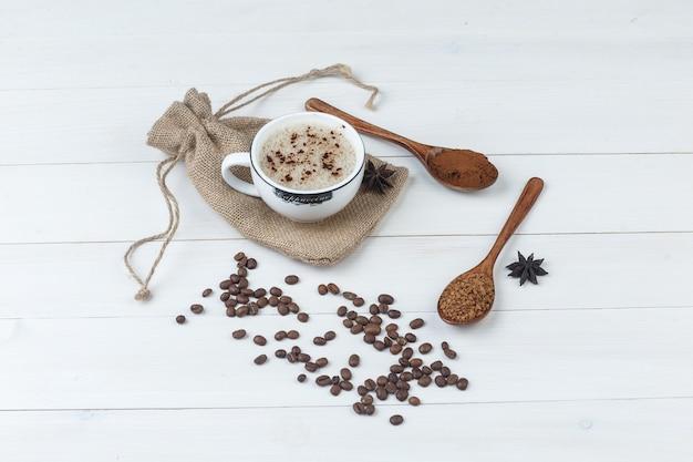 Um pouco de café com café moído, especiarias, grãos de café em uma xícara no fundo de madeira e saco, vista de alto ângulo.
