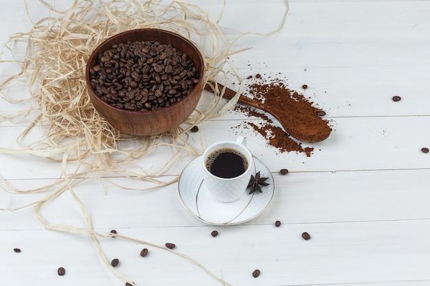 Um pouco de café com café moído, grãos de café, especiarias em uma xícara com fundo de madeira, vista de alto ângulo.