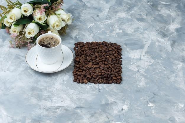 Um pouco de café com grãos de café, flores em uma xícara sobre fundo de mármore azul, vista de alto ângulo.