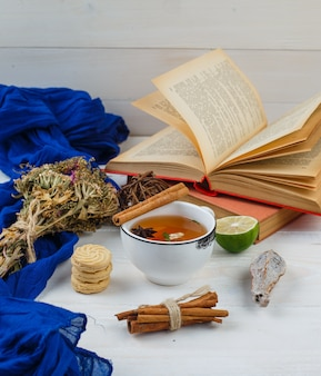 Um pouco de chá de ervas, biscoitos e flores com livros, limão, especiarias e lenço azul