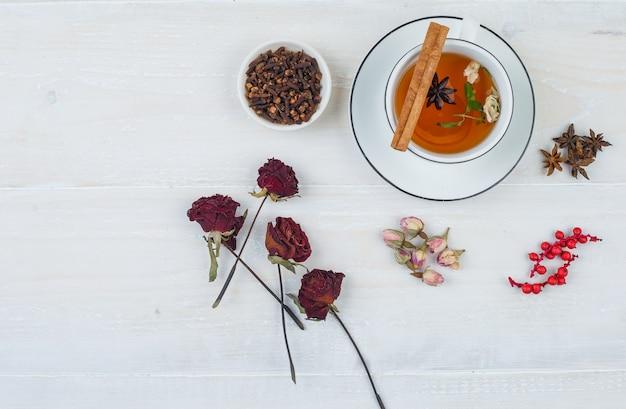 Um pouco de chá de ervas e rosas com botões de rosa, ervas e especiarias na superfície branca
