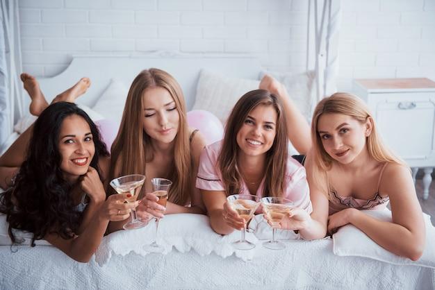 Um pouco de champanhe não irá interferir. meninas alegres na roupa de dormir deitada na cama no quarto branco e comemorar