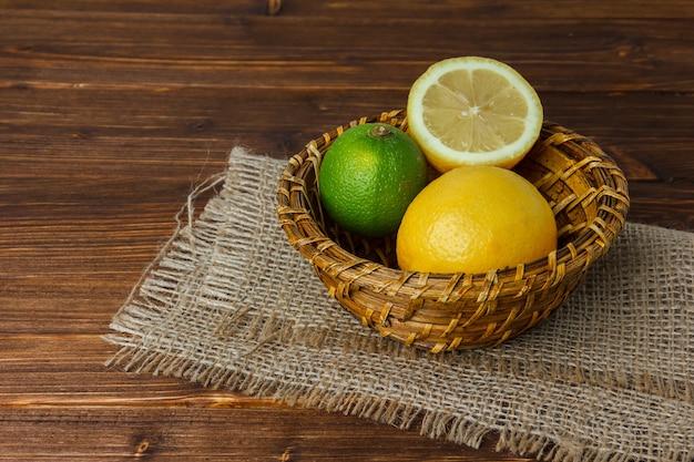 Um pouco de limão com metade do limão em um pedaço de saco em uma cesta na superfície de madeira, vista de alto ângulo. espaço para texto