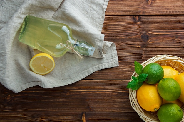 Um pouco de limão com uma garrafa de suco de limão, pano branco em uma cesta na superfície de madeira, vista superior. espaço para texto