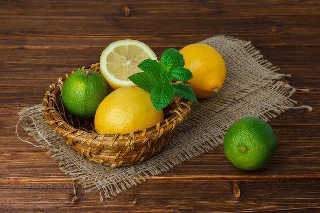 Um pouco de limão e folhas com metade do limão em um pedaço de saco em uma cesta na superfície de madeira, vista de alto ângulo. espaço para texto