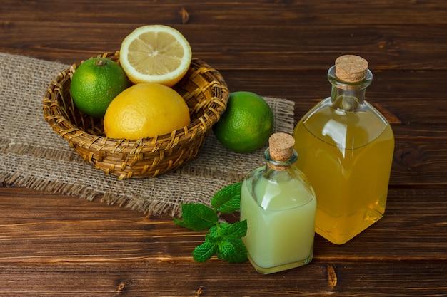Um pouco de limão e suco com metade do limão em um pedaço de saco em uma cesta na superfície de madeira, vista de alto ângulo. espaço para texto