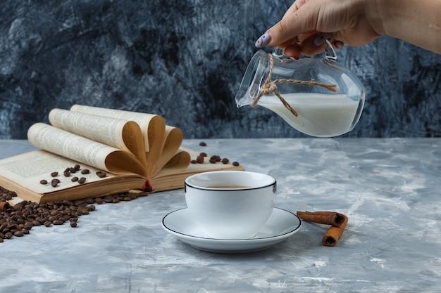 Um pouco de mão derramando leite em uma xícara de café com grãos de café, paus de canela, livro sobre grunge e fundo de gesso, vista lateral.