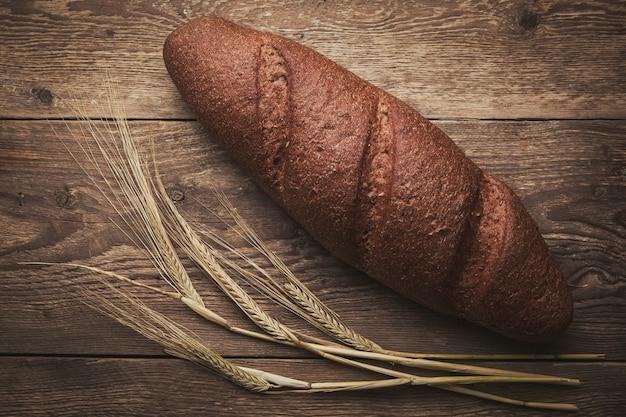 Um pouco de pão e trigo na configuração de madeira, plana.