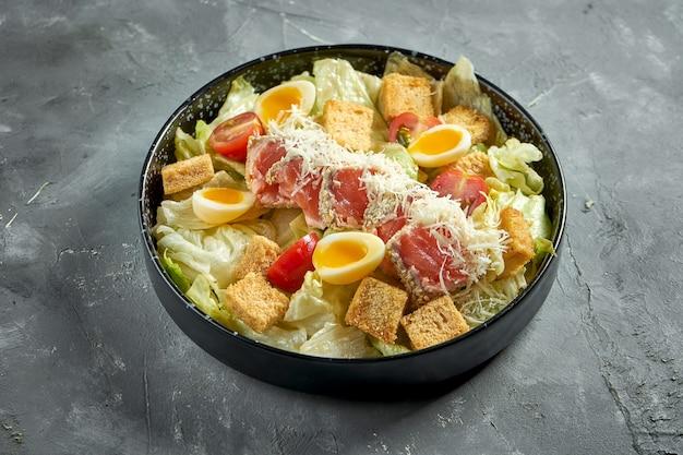 Um prato americano clássico - salada caesar com salmão, croutons, parmesão e tomate em um prato preto sobre uma superfície cinza